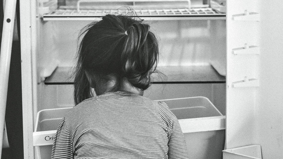 Kind vor leerem Kühlschrank