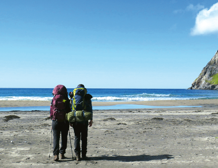 Zwei Wanderer an dem Sandstrand von Kvalvika