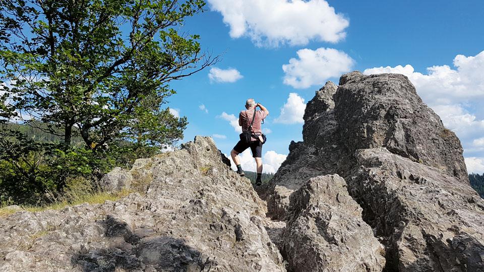 Mann schaut auf einem Felsen in die Ferne