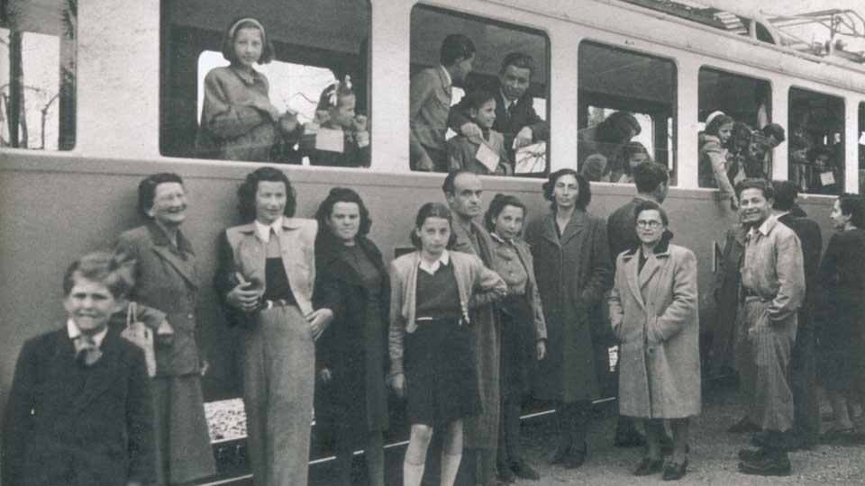 schwarz-weiß Bild der Zeitgeschichte: Menschen vor alter Straßenbahn