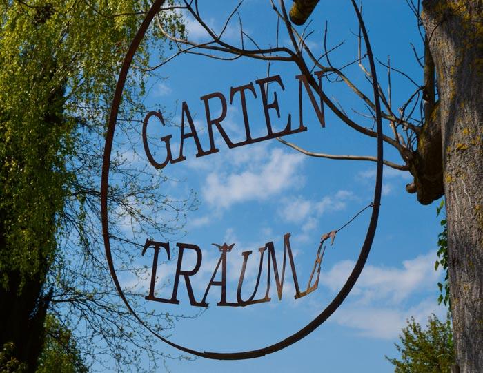 Schild: Gartenträume an einem Baum befestigt