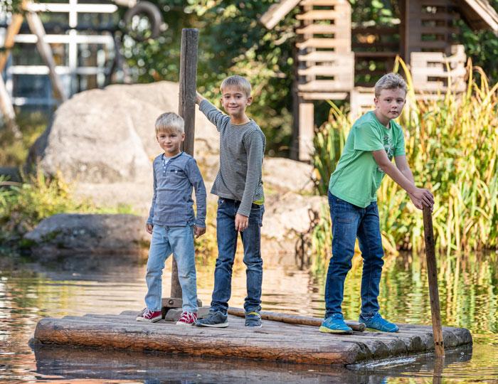 Ein Holz-Floß mit drei Jungs