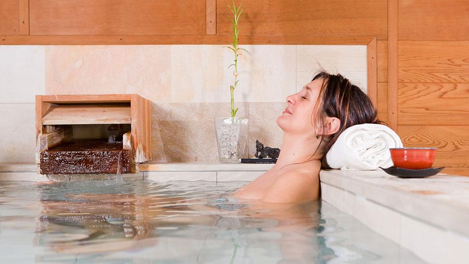 Frau beim entspannen in einem japanischen Thermalbad