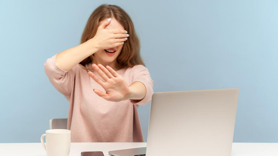 Frau hält sich Augen zu sitz vor Laptop