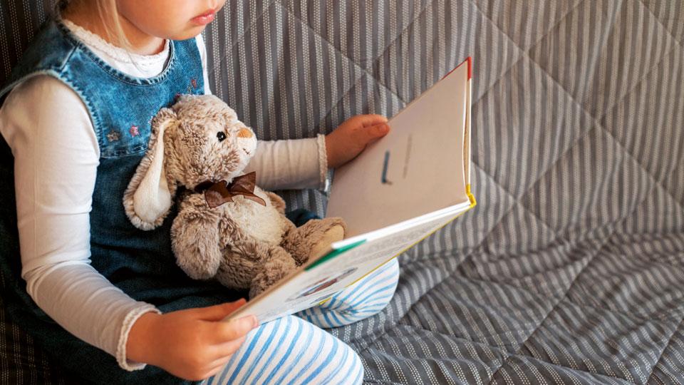 Kind mit Buch und Kuscheltier