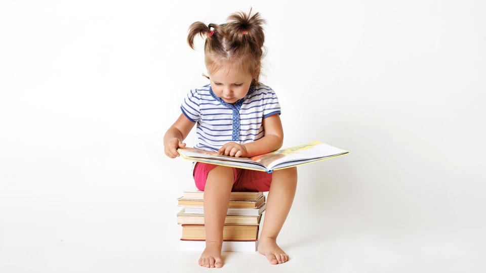 Kind sitzt auf Bücherstapel
