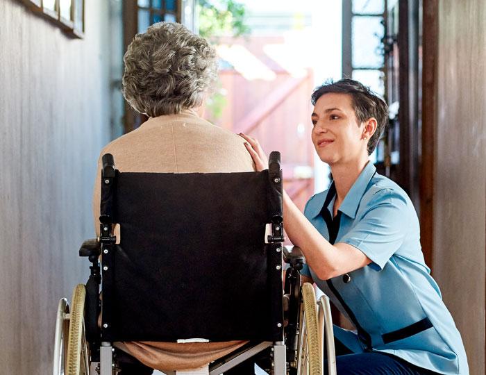 Frau im Rollstuhl mit Pflegerin
