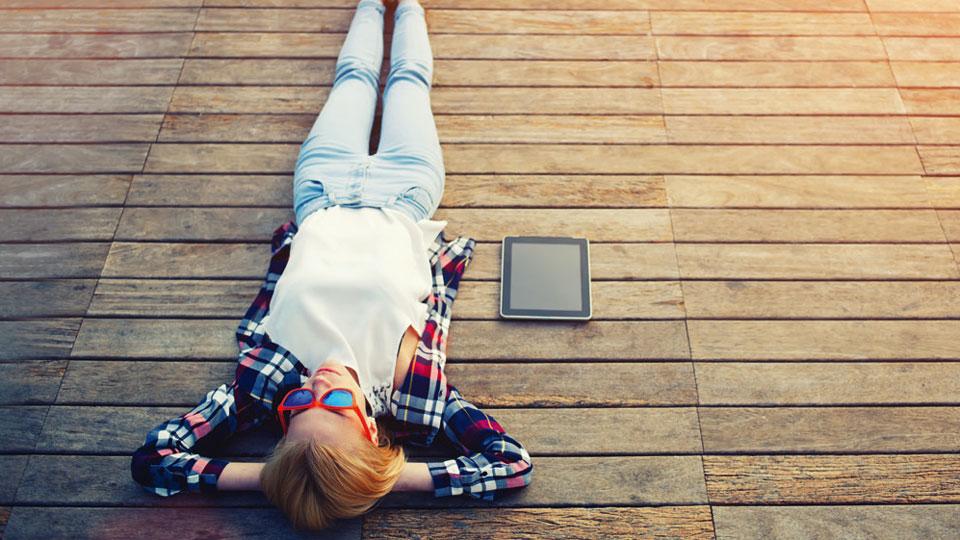 Junge Frau entspannt auf Holzpier