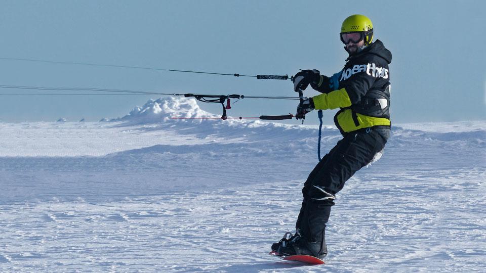 Mann mit Lenkdrachen im Schnee
