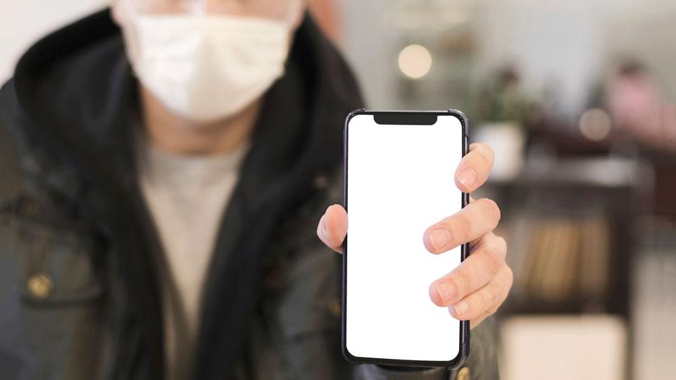Mann mit Handy und Mundschutz
