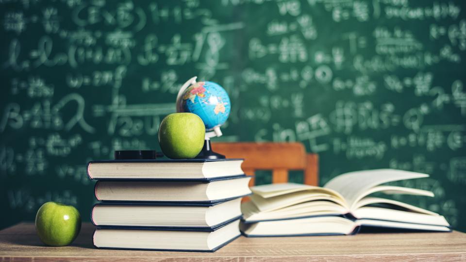 beschriebene Tafel mit Büchern und Äpfeln im Vordergrund