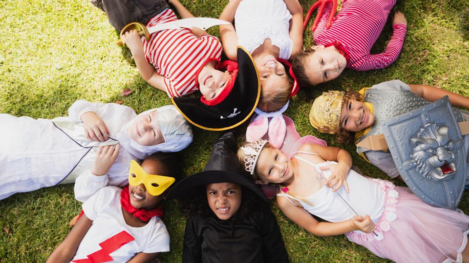 Verkleidete Kinder, die im Kreis liegen