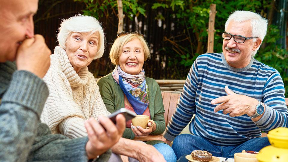 zwei Frauen und Männer sitzen föhlich bei einder Tasse Kaffee zusammen
