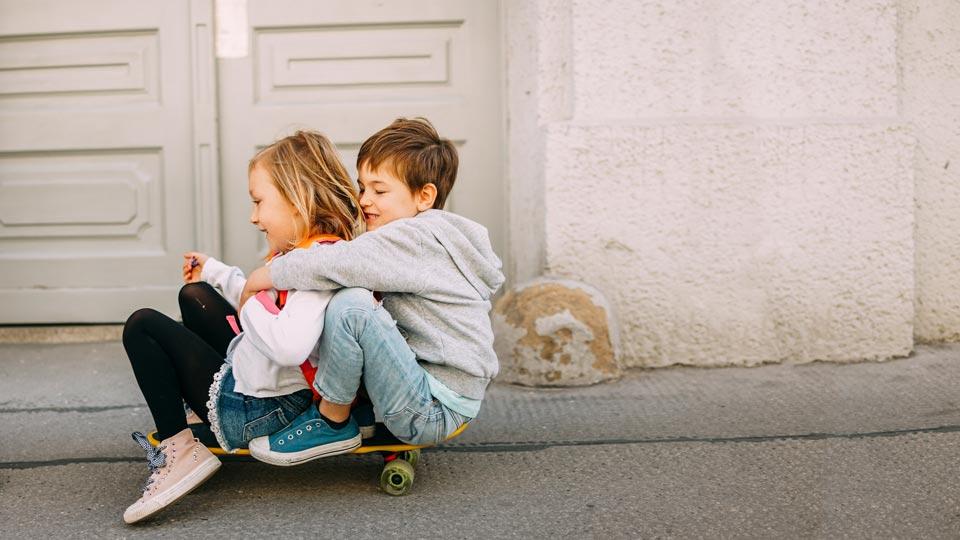 zwei Geschwister auf einem Skateboard