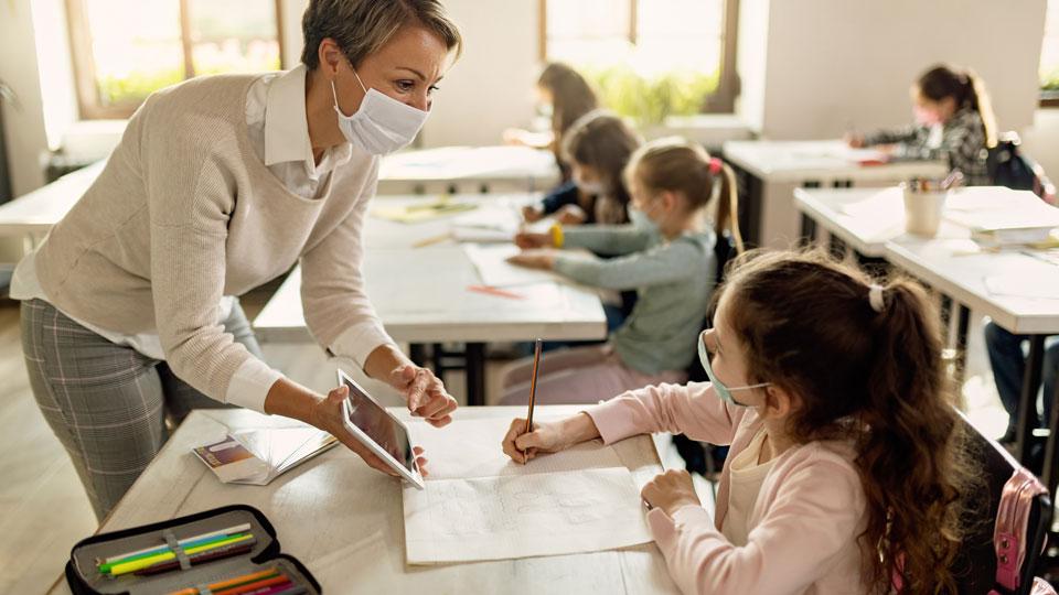 Schüler im Unterricht mit der Hilfe von einer Lehrerin