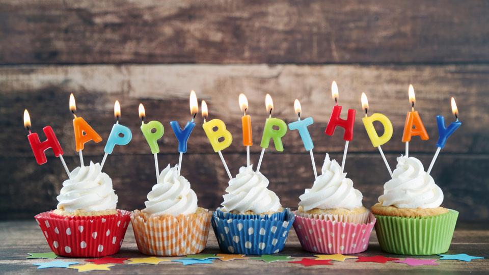 """Muffins mit Kerzen die """"Happy Birthday"""" buchstabieren"""