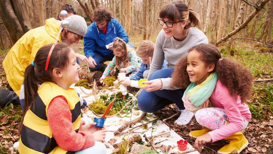 Kinder und Erwachsene beim Spielen im Wald