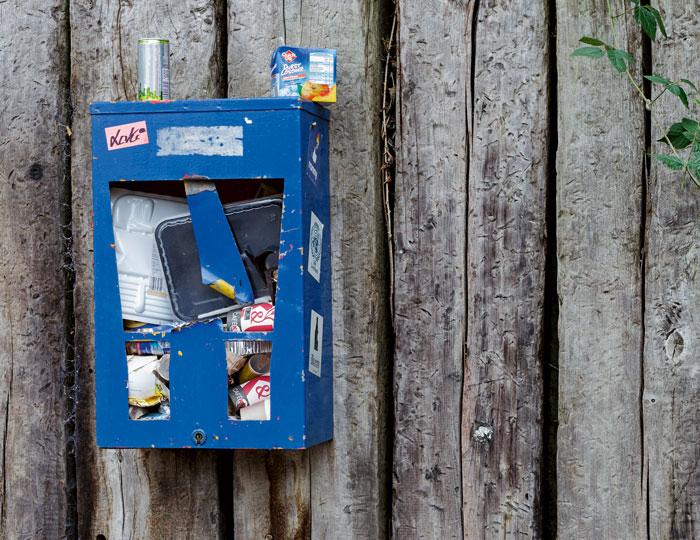 Blauer, kaputter und als Mülleimer umfunktionierter Kaugummiautomat