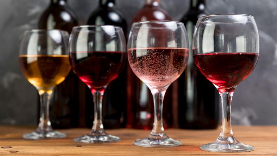 Wein in Gläsern mit den passenden Flaschen im Hintergrund