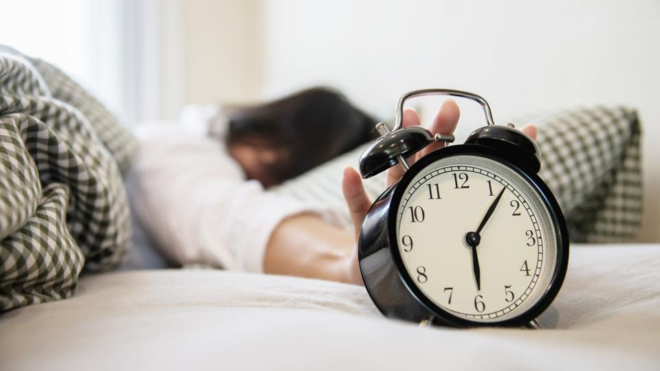 Frau im Halbschlaf, die ihren Wecker sucht