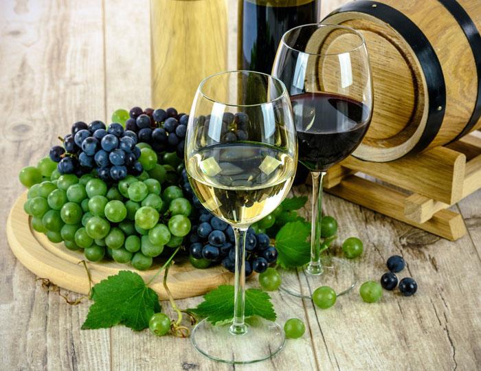 Weingläser, Trauben und ein Weinfass
